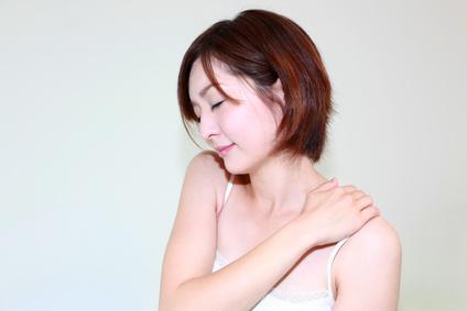 つらい肩こりの症状に悩む女性