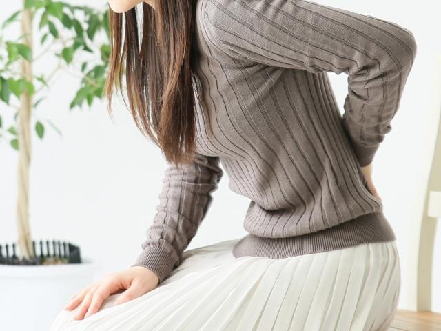腰痛のつらい症状に悩む女性