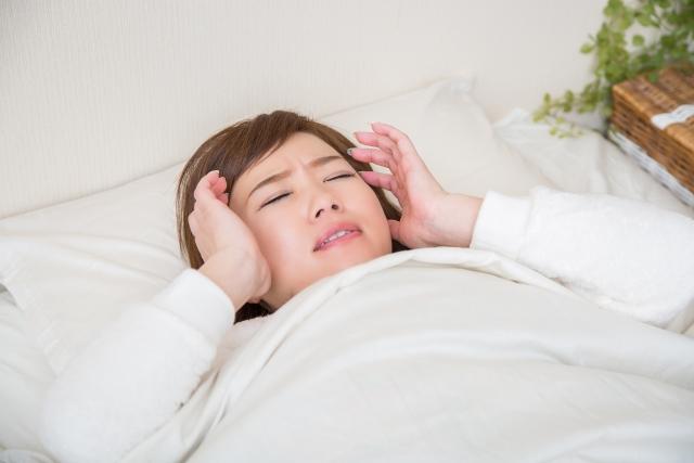 酷い頭痛で眠れなくて悩んでいる女性
